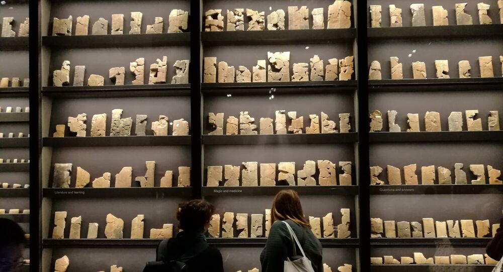 Visitors walk past a collection of 7th-century cuneiform texts from Ashurbanipal's personal library.