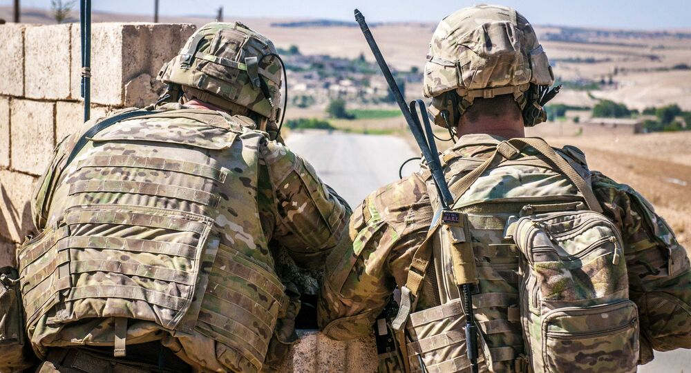 Two U.S. Soldiers keep an eye on the demarcation line during a security patrol outside Manbij, Syria, June 26, 2018