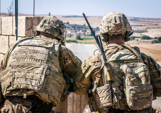 Two US soldiers keep an eye on the demarcation line during a security patrol outside Manbij, Syria, 26 June, 2018