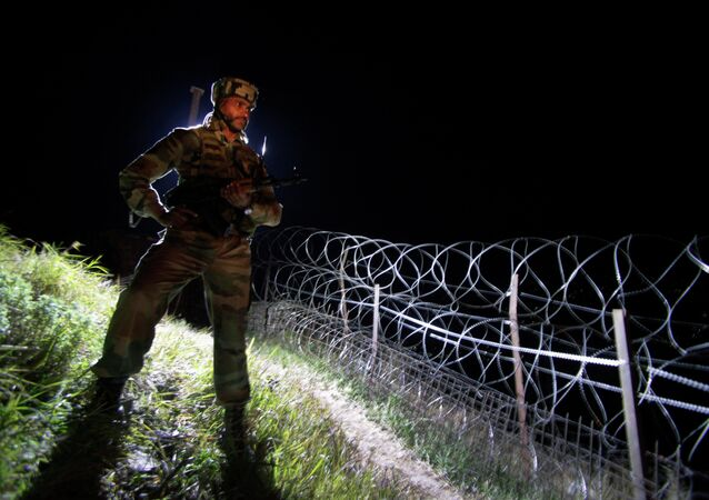 an Indian army soldier stands guard along barbed wire near the Line of Control (LOC), that divides Kashmir between India and Pakistan