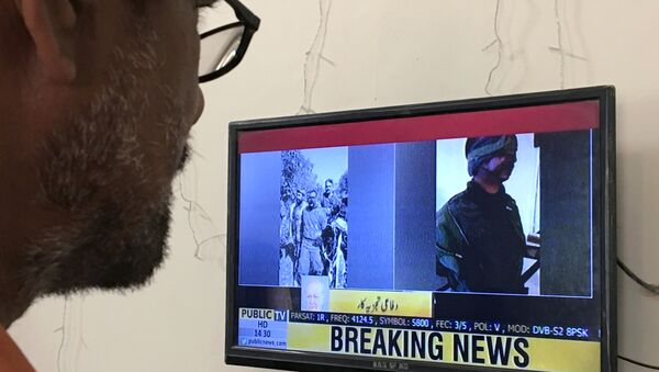 A man looks at a television screen displaying the pictures of the Indian pilots, said to be captured by Pakistan after shooting down two Indian planes, in Karachi, Pakistan February 27, 2019 - Sputnik International