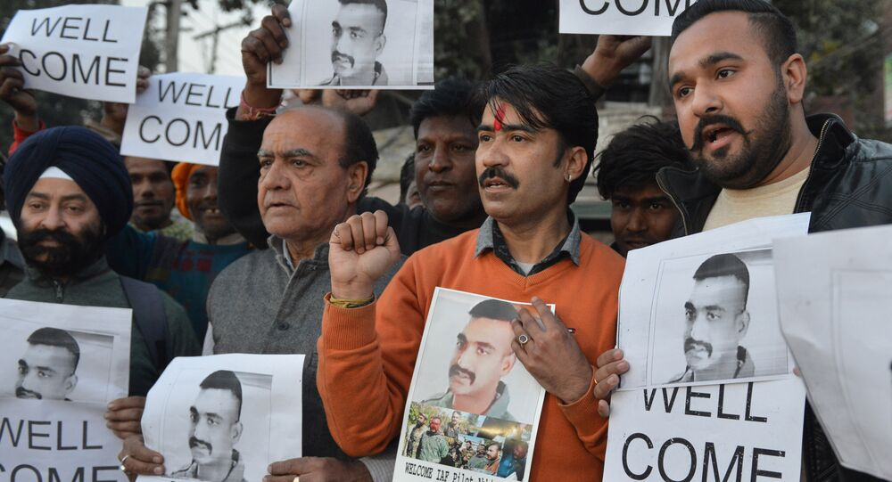 Indian people hold placards and photographs of Indian Air Force pilot Abhinandan Varthaman, as they celebrate the announcement of his soon release, in Amritsar on February 28, 2019.