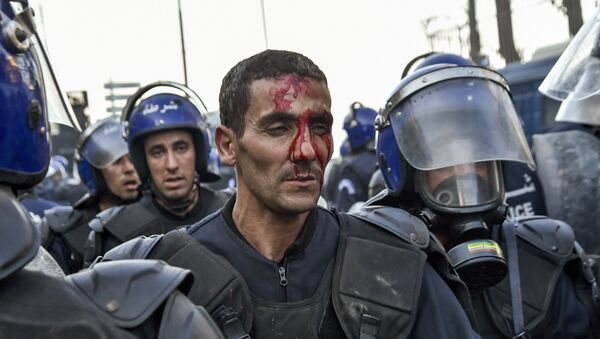 A member of the Algerian security forces is seen with a bloodied face as riot forces respond to protests in the capital Algiers on March 1, 2019, against ailing President Abdelaziz Bouteflika's bid for a fifth term in power. - Sputnik International