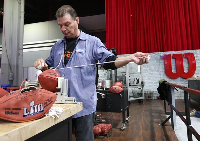 Wilson employee Brad Hanna works on lacing a Super Bowl LIII footballs during the NFL Experience at Georgia World Congress Center.