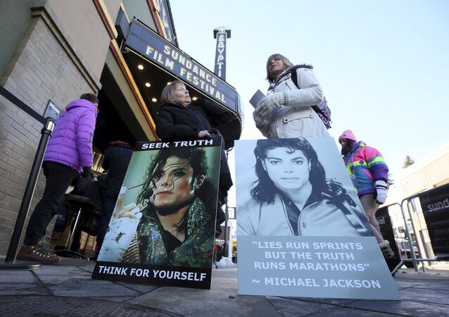 In this Jan. 25, 2019, file photo Brenda Jenkyns, left, and Catherine Van Tighem who drove from Calgary, Canada stand with signs outside of the premiere of the Leaving Neverland Michael Jackson documentary film at the Egyptian Theatre on Main Street during the 2019 Sundance Film Festival in Park City, Utah