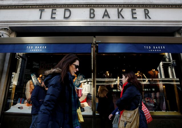 Shoppers walk past a Ted Baker store on Regents Street in London