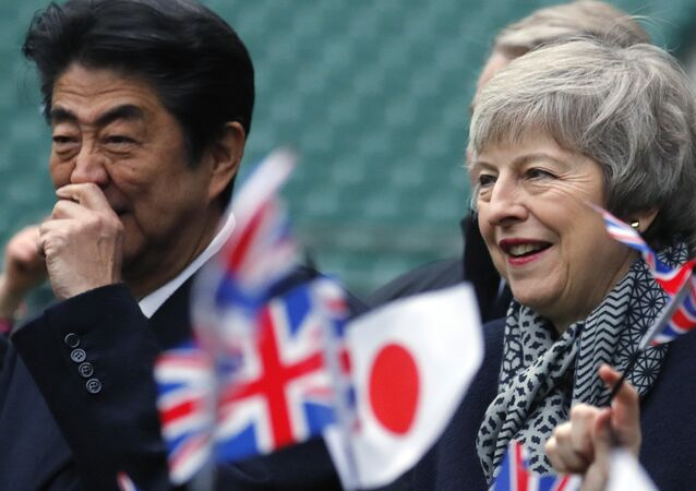 Britain's Prime Minister Theresa May, right and Japanese Prime Minister Shinzo Abe are greeted by Chase Bridge Primary School children waving flags, during a visit to Twickenham Rugby Stadium, in London, Thursday, Jan. 10, 2019.