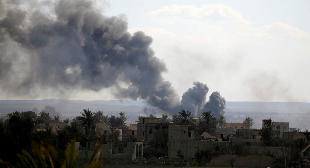 Black plumes of smoke rise in Baghouz, Deir Al Zor province