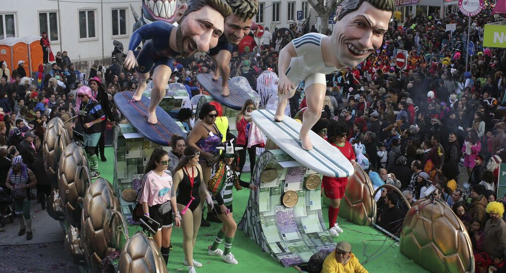 A float with sculptures of soccer players Lionel Messi, Neymar and Cristiano Ronaldo, from left to right, parades through the street during Carnival celebrations in Torres Vedras, north of Lisbon, Tuesday, Feb. 13 2018