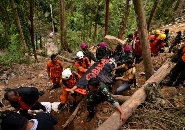 Rescue workers carry a body bag containing a victim after the landslide of the illegal gold mine at Bolaang Mongondow Regency in North Sulawesi, Indonesia, February 28, 2019