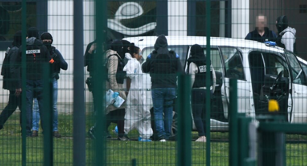 Michaël Chiolo, wearing a white forensic jumpsuit, is escorted into custody after the incident at Condon-sur-Sarthe prison