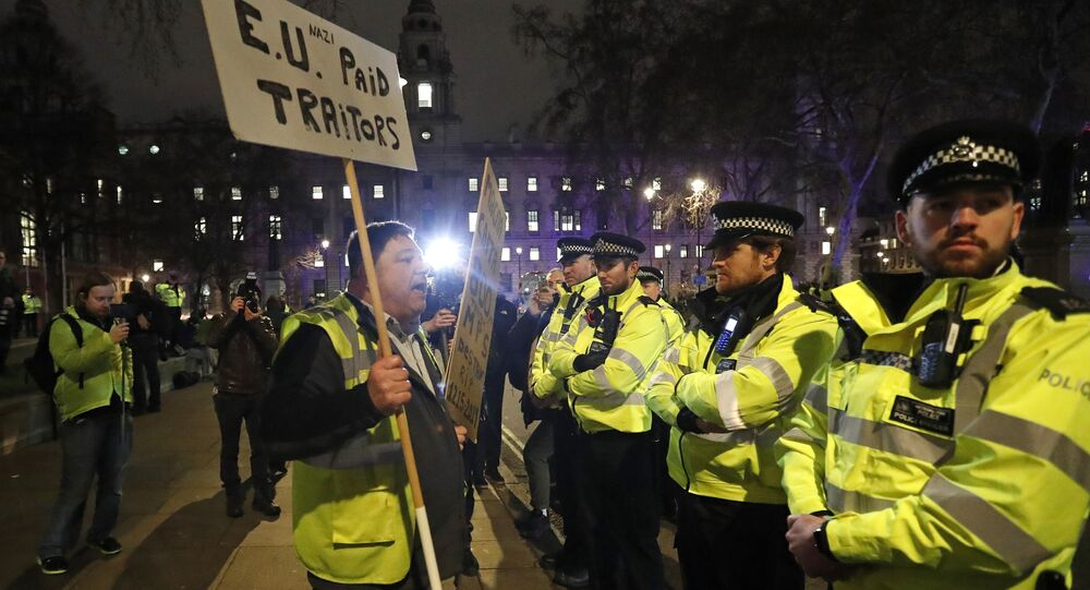 An pro-Brexit demonstrator confronts police officers in Parliament square in London, Tuesday, Jan. 15, 2019.