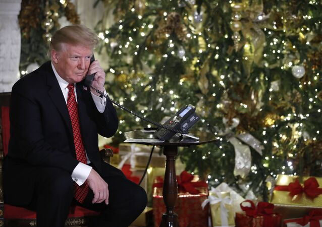 President Donald Trump listens on the phone as he shares updates to track Santa's movements from the North American Aerospace Defense Command (NORAD) Santa Tracker on Christmas Eve, 2018