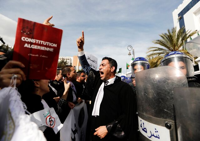 Lawyers chant slogans as they gesture near riot police outside the constitutional council during a protest denouncing an offer by President Abdelaziz Bouteflika to run in elections next month but not to serve a full term if re-elected, in Algiers, Algeria March 7, 2019.