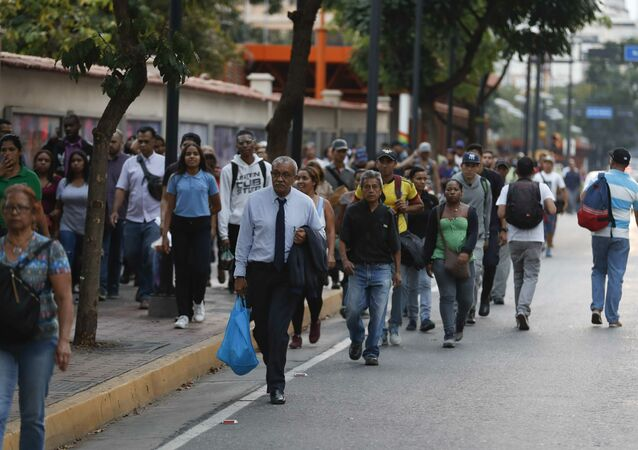 People walking along an avenue after a power outage in Caracas, Venezuela, Thursday, March 7, 2019. A power outage left much of Venezuela in the dark early Thursday evening in what appeared to be one of the largest blackouts yet in a country where power failures have become increasingly common