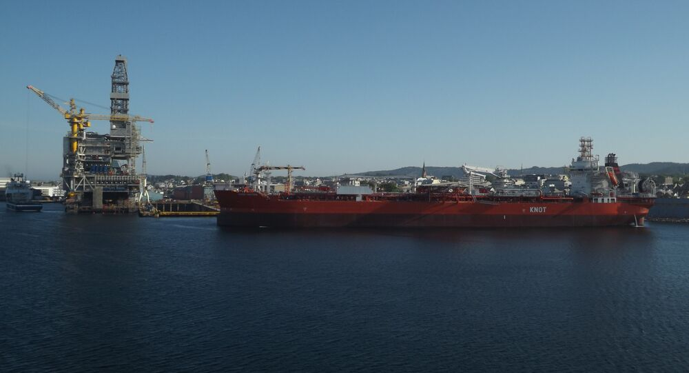 A KNOT oil tanker sails past a refinery in the Norwegian fjords.