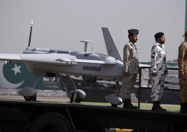 Pakistani soldiers stand beside a manufactured armed drone aircraft loaded on a vehicle is on display during a military parade in Islamabad, Pakistan, Friday, March 23, 2018.