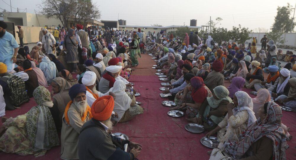 Sikh pilgrim wait for food at the shrine of their spiritual leader Guru Nanak Dev in Kartarpur, Pakistan, Wednesday, Nov. 28, 2018.