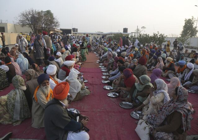 Sikh pilgrim wait for food at the shrine of their spiritual leader Guru Nanak Dev in Kartarpur, Pakistan. File photo