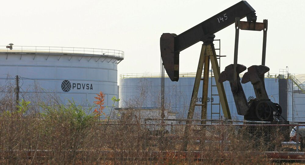 An oil pumpjack and a tank with the corporate logo of state oil company PDVSA are seen in an oil facility in Lagunillas