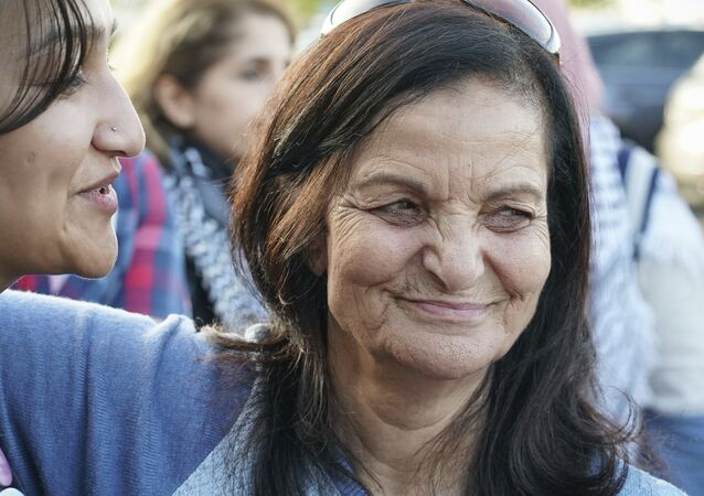 Rasmea Odeh, right, hugs a supporter before boarding a flight to Amman on Tuesday, Sept. 19, 2017.