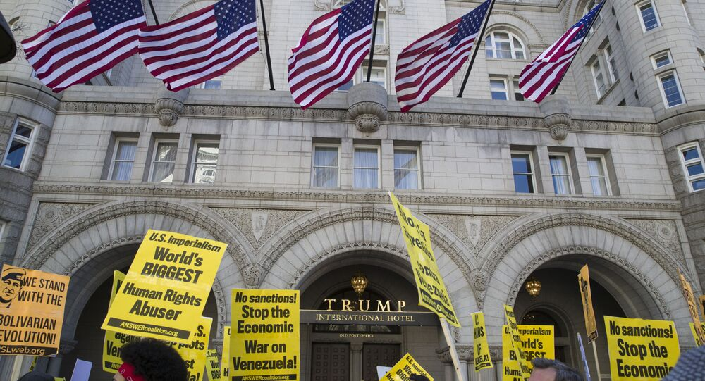 Activists walk past the front of the Trump International Hotel during the, Hands Off Venezuela!, 16 March, 2019, Washington