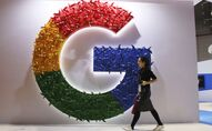In this 5 November 2018, photo, a woman carries a fire extinguisher past the logo for Google at the China International Import Expo in Shanghai