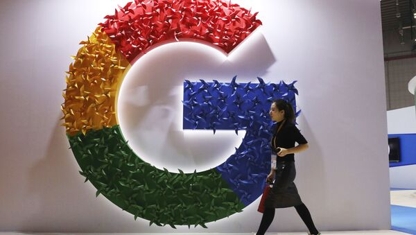 In this 5 November 2018, photo, a woman carries a fire extinguisher past the logo for Google at the China International Import Expo in Shanghai - Sputnik International