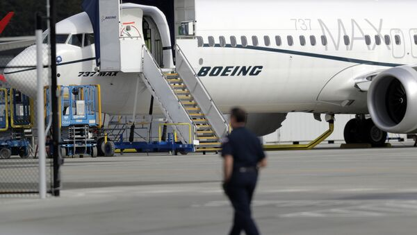 A worker walks next to a Boeing 737 MAX 8 airplane parked at Boeing Field, Thursday, March 14, 2019, in Seattle - Sputnik International