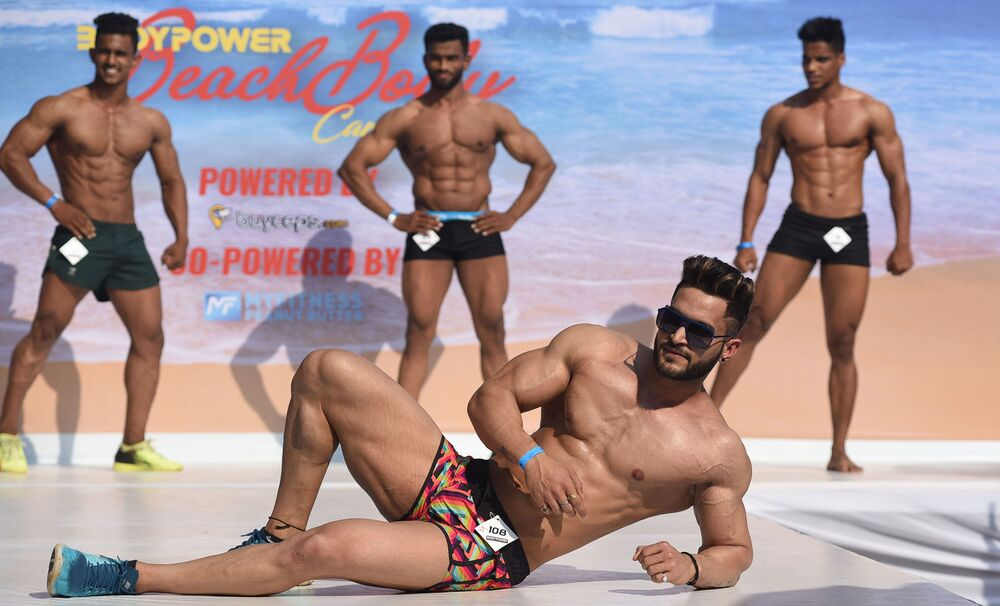 Indian male fitness models perform on stage during the 'Body Power Beach Show'