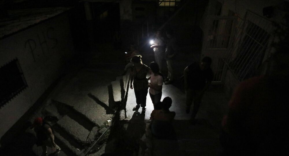 Residents stand outside during a blackout in the Santa Cruz of the East neighborhood, in Caracas, Venezuela, Thursday, March 14, 2019.
