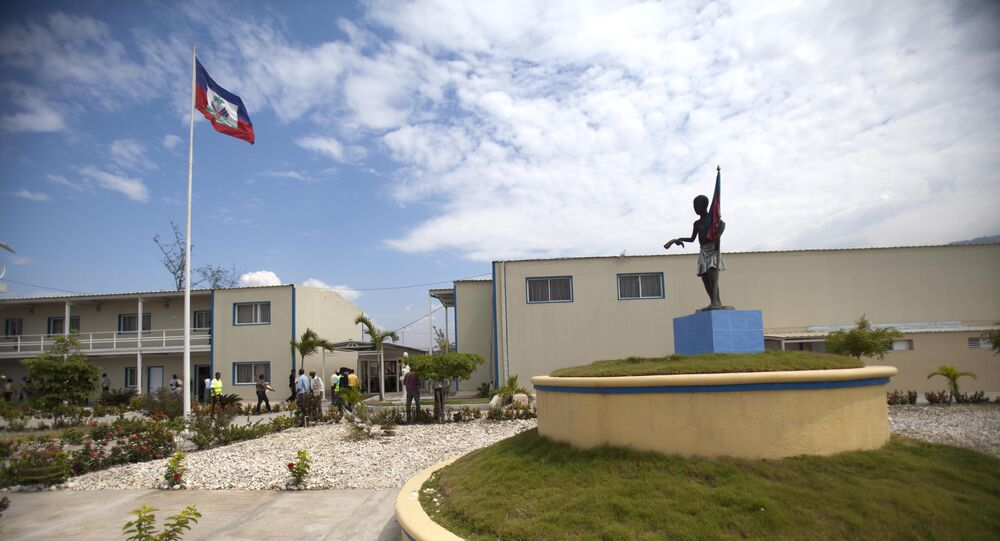 In this March 15, 2013 photo, Haiti's national flag flies outside parliament which was renovated by Chemonics International Inc., a for-profit international development company based in Washington D.C., in downtown of Port-au-Prince, Haiti.