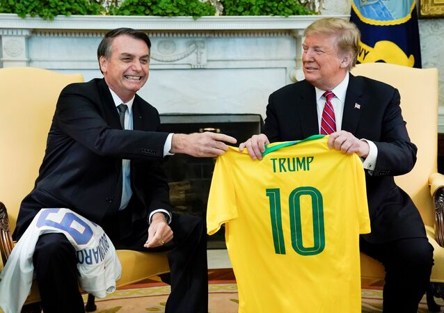 Brazil's President Jair Bolsonaro presents a Brazil naitonal soccer team jersey to US President Donald Trump after Trump gave him a US soccer team jersey during a meeting in the Oval Office of the White House in Washington, US, March 19, 2019.