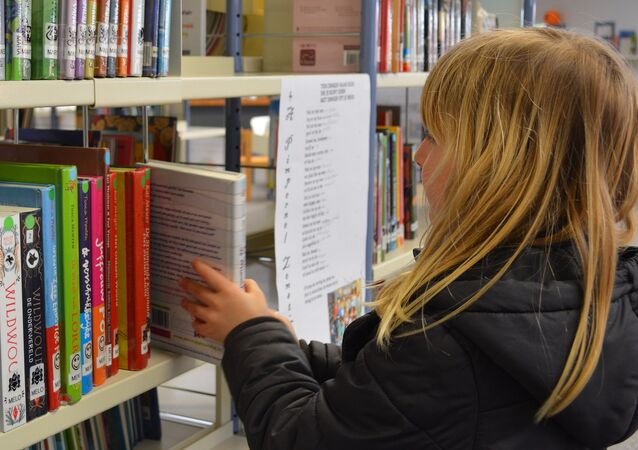 A young girl picking up a book