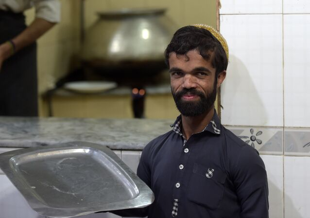In this picture taken on February 22, 2019, Rozi Khan, a 25-year-old Pakistani waiter who resembles US actor Peter Dinklage, looks on at Dilbar Hotel in Rawalpindi.