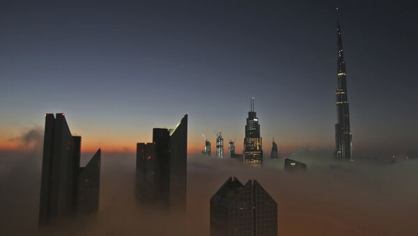 The sun rises over the city skyline with the Burj Khalifa, world's tallest building at the backdrop, seen from a balcony on the 42nd floor of a hotel on a foggy day in Dubai, United Arab Emirates, Saturday, Dec. 31, 2016 - Sputnik International