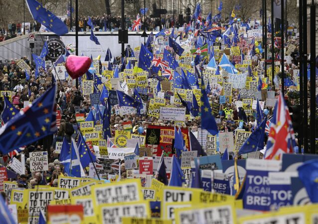 Demonstrators carry posters and flags during a Peoples Vote anti-Brexit march in London, Saturday, March 23, 2019