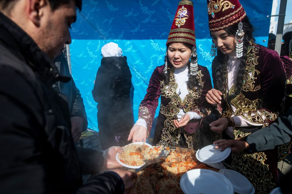 Girls Wearing National Outfits Treat Attendees With Pilaf During Celebrations of Nowruz at Independence Square in Nur-Sultan