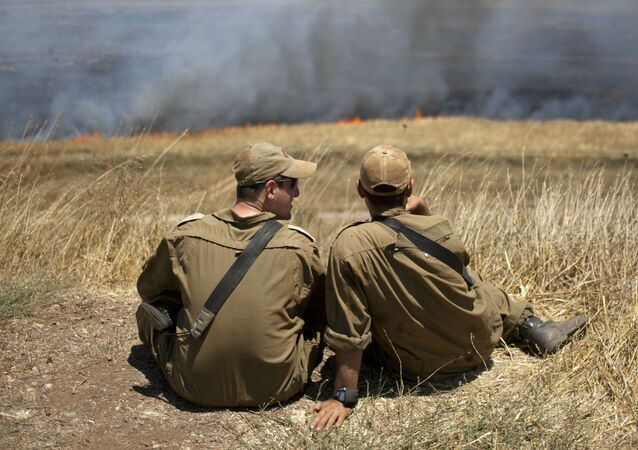 Israeli soldiers sit in a position on the Israeli-controlled Golan Heights as smoke rises following explosions of mortar shells (File)