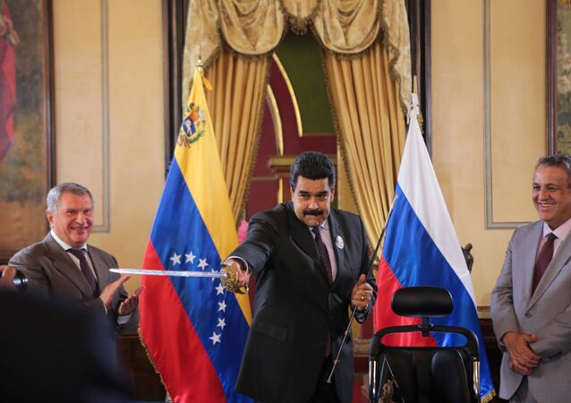 Venezuela's President Maduro holds a replica of Venezuela's national hero Simon Bolivar's sword as Head of Rosneft Igor Sechin and Venezuela's Oil Minister and President of PDVSA Eulogio del Pino look on in Caracas