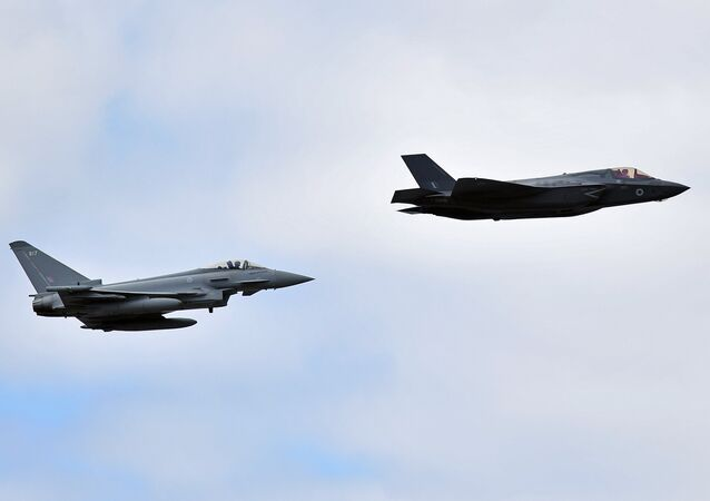 A British Royal Air Force (RAF) Lockheed Martin F-35 Lightning II (R) and a Eurofighter Typhoon aircraft perform a fly-past during the Farnborough Airshow, south west of London, on July 17, 2018