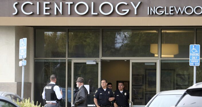 Police stand by outside and investigators work inside the entrance to the Church of Scientology in Inglewood, Calif., Wednesday, March 27, 2019.