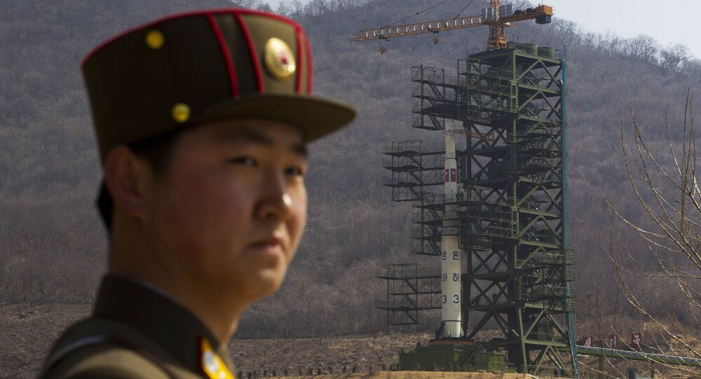 A North Korean soldier stands in front of the country's Unha-3 rocket, slated for liftoff between April 12-16, at a launching site in Tongchang-ri, North Korea on Sunday April 8, 2012.