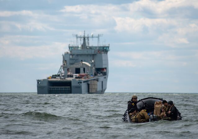 Sailors assigned to Explosive Ordnance Disposal Mobile Unit (EODMU) 2 man a combat rubber raiding craft while underway with the Royal Fleet Auxiliary landing ship dock Mounts Bay during a mine countermeasures (MCM) task group experiment.