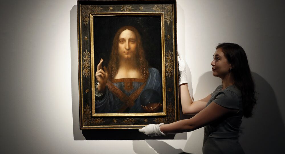 In this Oct. 24, 2017 file photo, an employee poses with Leonardo da Vinci's Salvator Mundi on display at Christie's auction rooms in London.