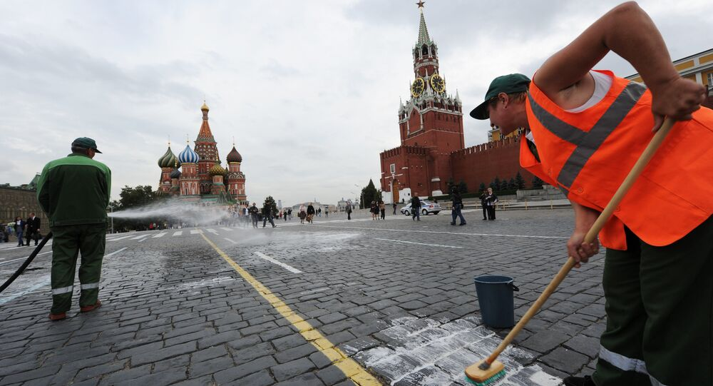 Communal services worker washes the cobblestones of Red Square in Moscow with soap