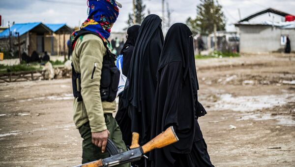 Foreign women, living in al-Hol camp which houses relatives of Islamic State (IS) group members, walk under the supervision of a fighter of the Syrian Democratic Forces (SDF) in the camp in al-Hasakeh governorate in northeastern Syria on March 28, 2019 - Sputnik International