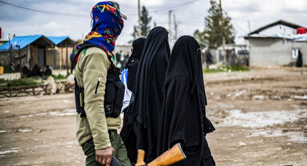 Foreign women, living in al-Hol camp which houses relatives of Islamic State (IS) group members, walk under the supervision of a fighter of the Syrian Democratic Forces (SDF) in the camp in al-Hasakeh governorate in northeastern Syria on March 28, 2019