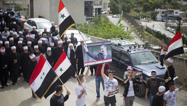 Druze men carry Syrian flags and pictures of Syrian President Bashar Assad during a rally marking Syria's Independence Day, in the Druze village of Ein Qiniyye, Israeli-controlled Golan Heights, Tuesday, April 17, 2018. - Sputnik International