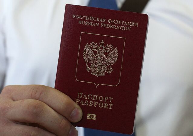 An employee of a passport and visa center demonstrates a foreign travel passport with additional biometric personal data